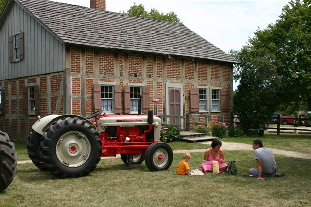 Small Family Dining Next to Old Tractor