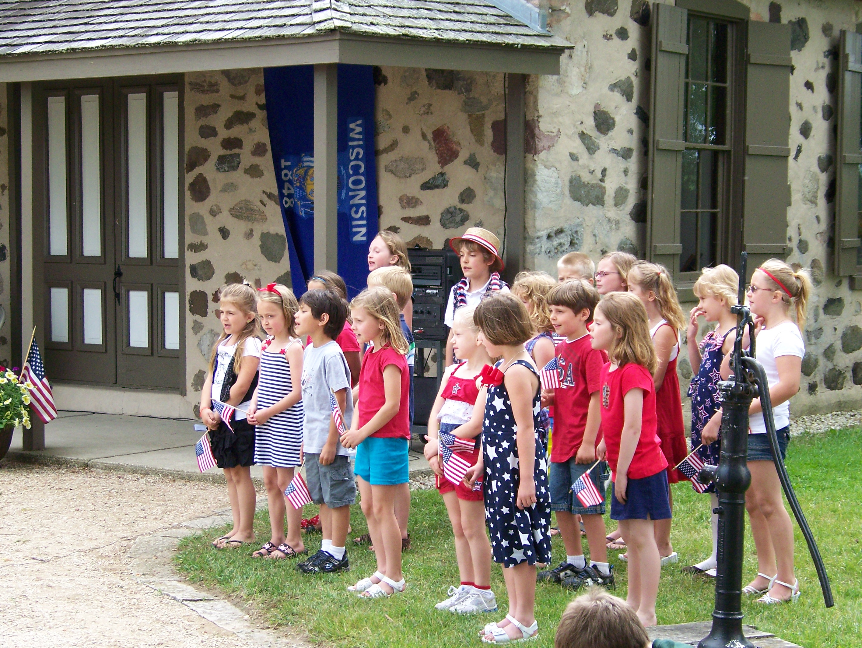 A Group of Patriotic Children Singing Outside