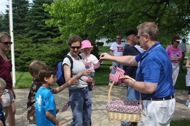 A Man with a Basket of Small American Flags