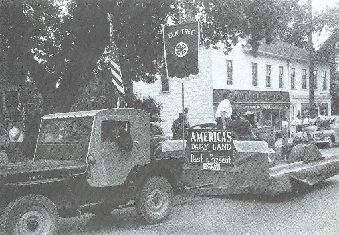 Central Dry Goods building pictured behind the America's Dairy Land Past and Present parade float.