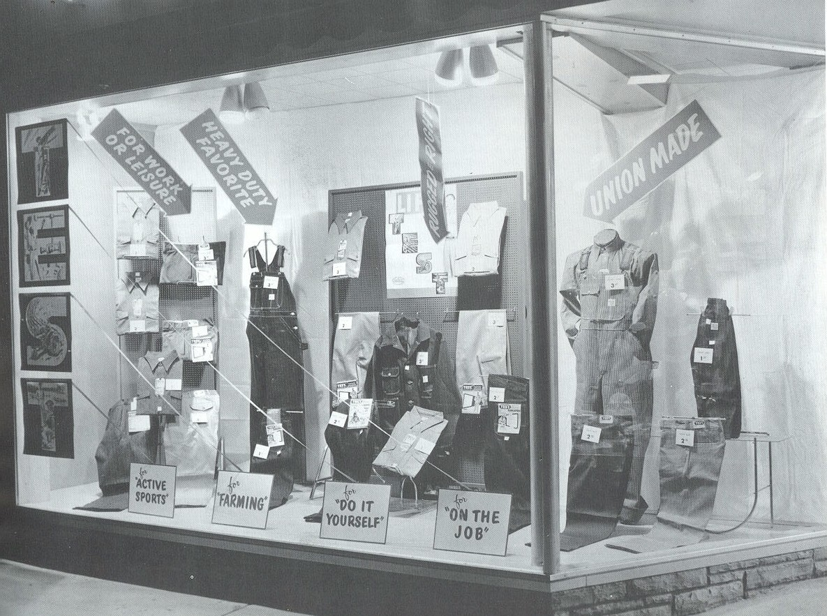 Window of Central Dry Goods with clothes and signs.