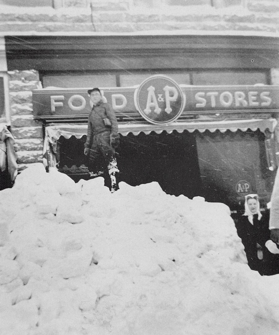 A person standing atop a high snowbank in front of what was Gerrit's Drug Store and the A&P Store.