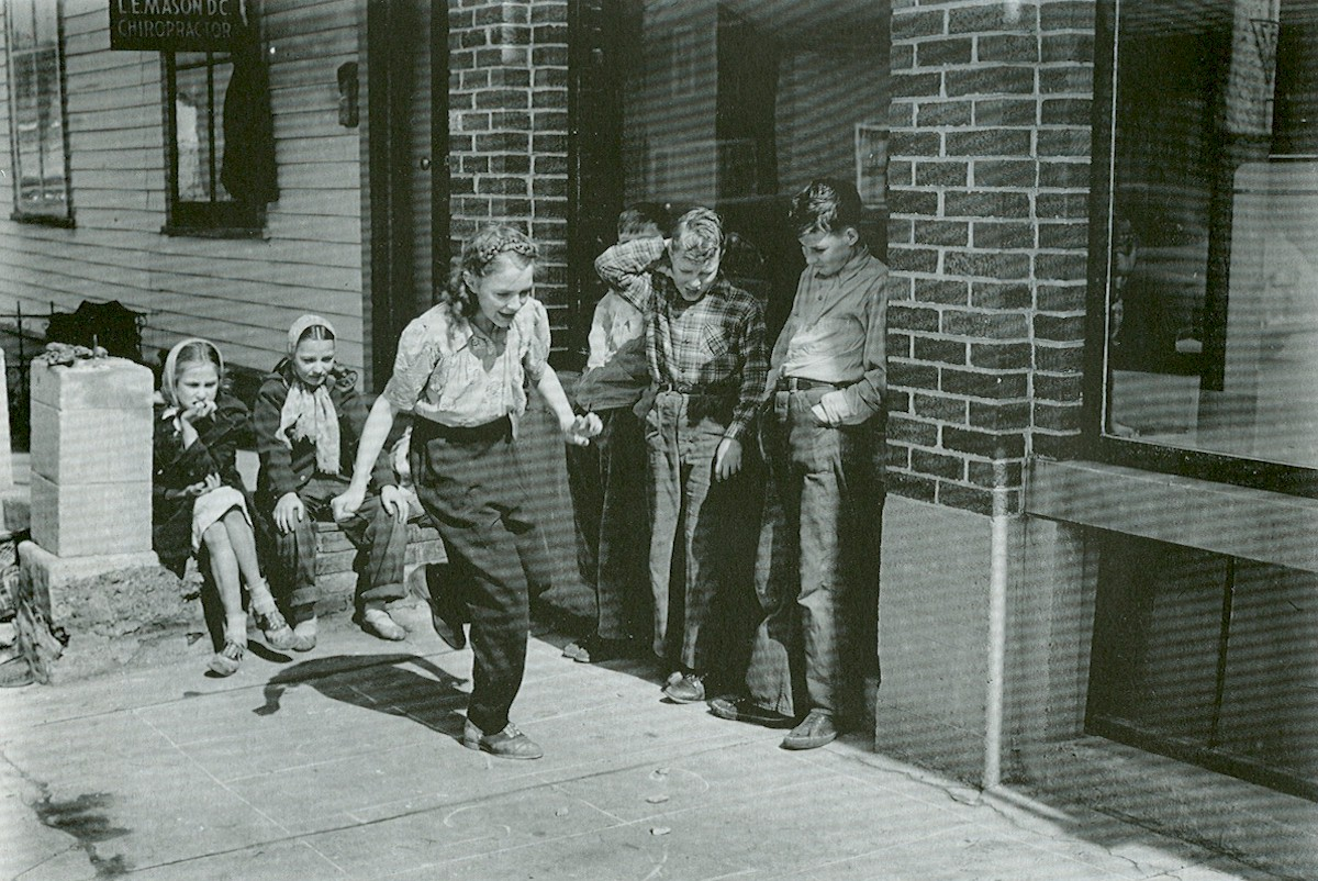 A group of children gathered to play hopscotch in front of the old Groth garage.