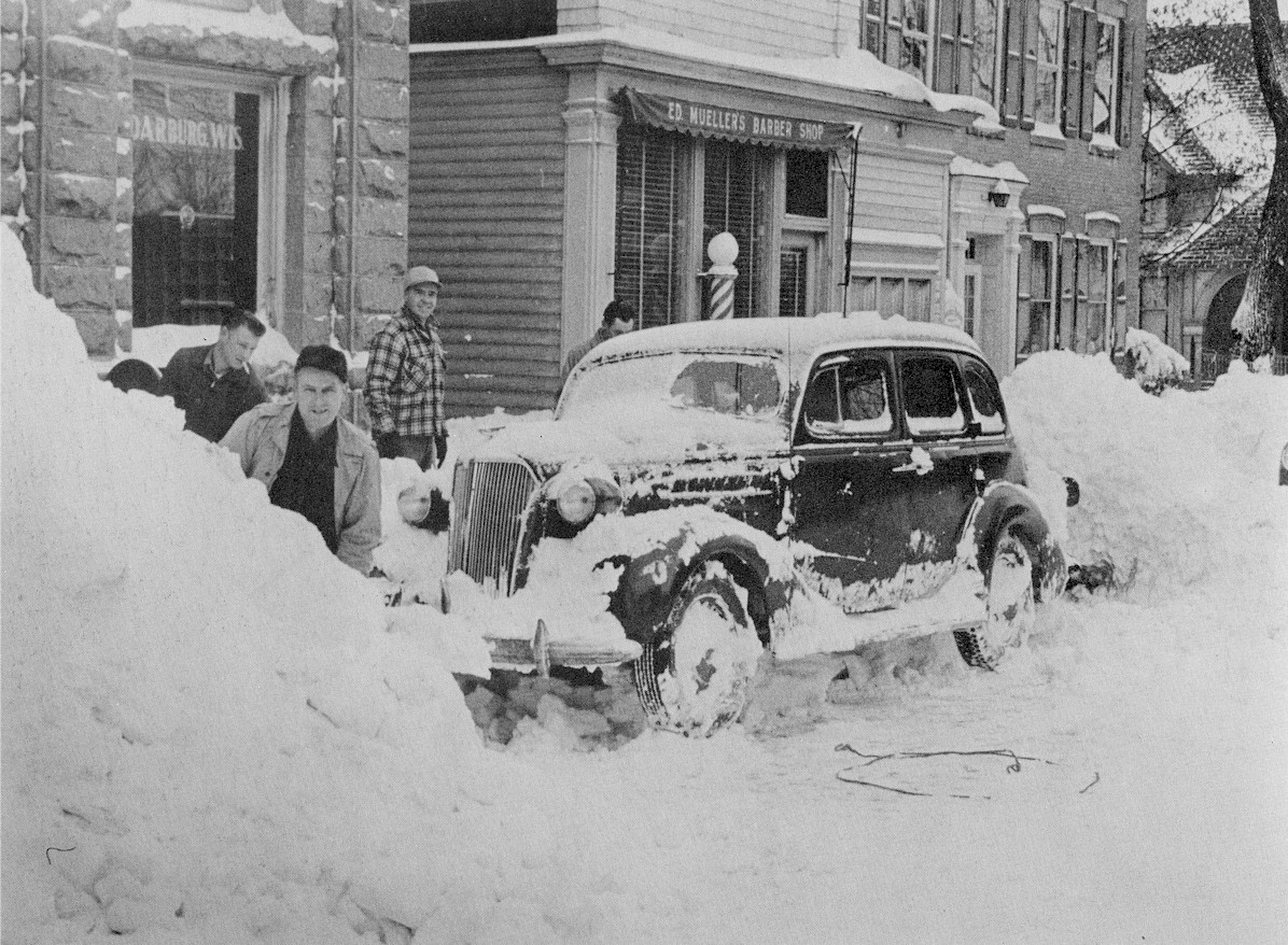 A car being dug out after being covered in snow.