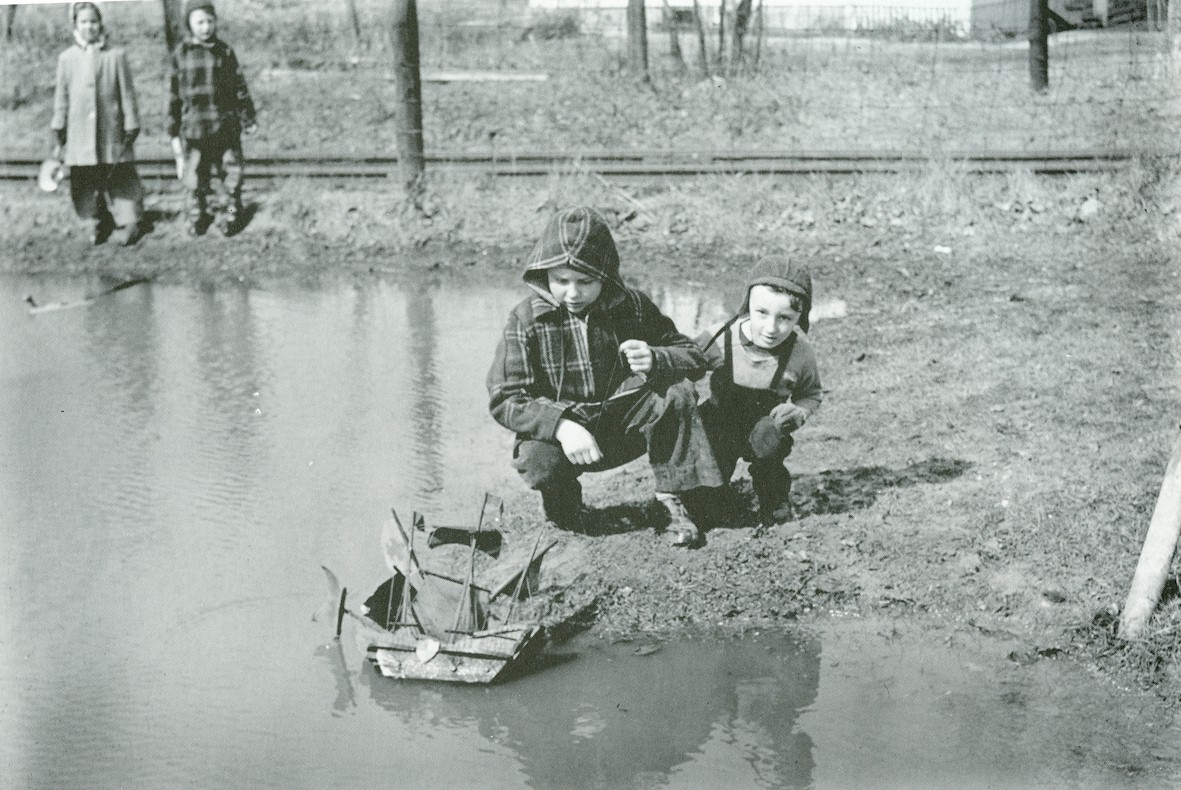 Kids playing with a toy sailboat in a puddle.