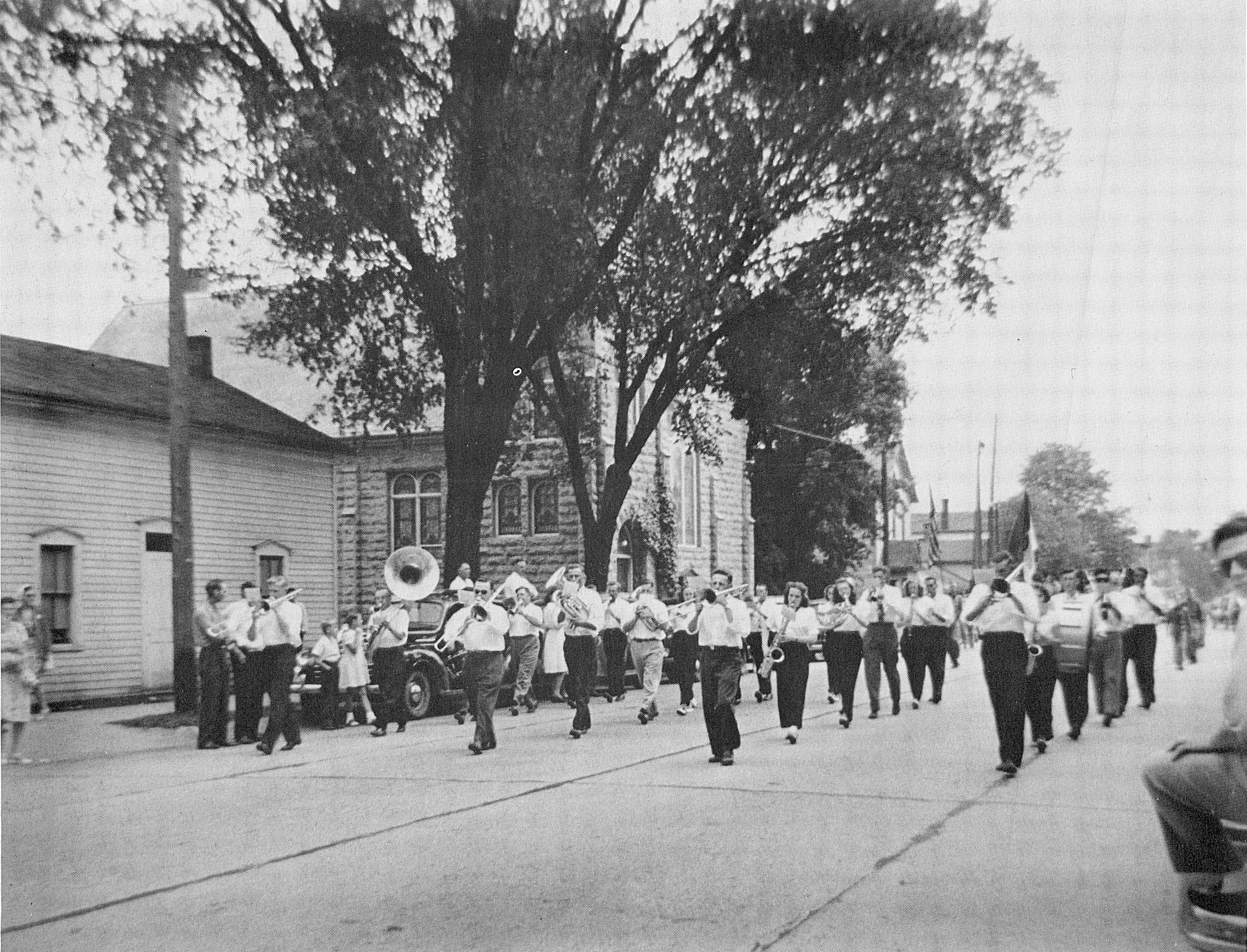 School band marching in a parade wearing conventional clothes.