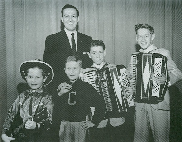Four boys and a man  prepared for the talent show with accordians and a guitar.