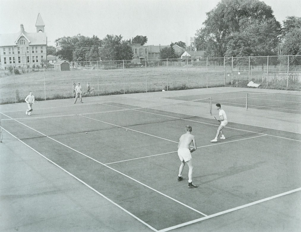 People playing a doubles match of tennis on a tennis court.