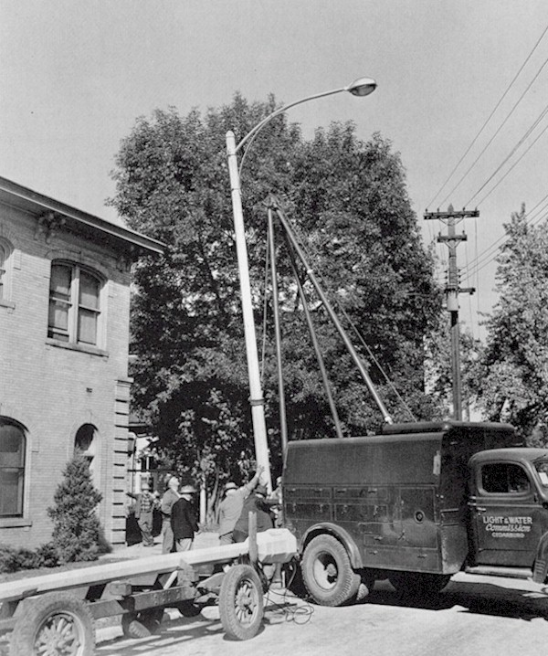 Men placing the new lamp posts with the help of a big truck.