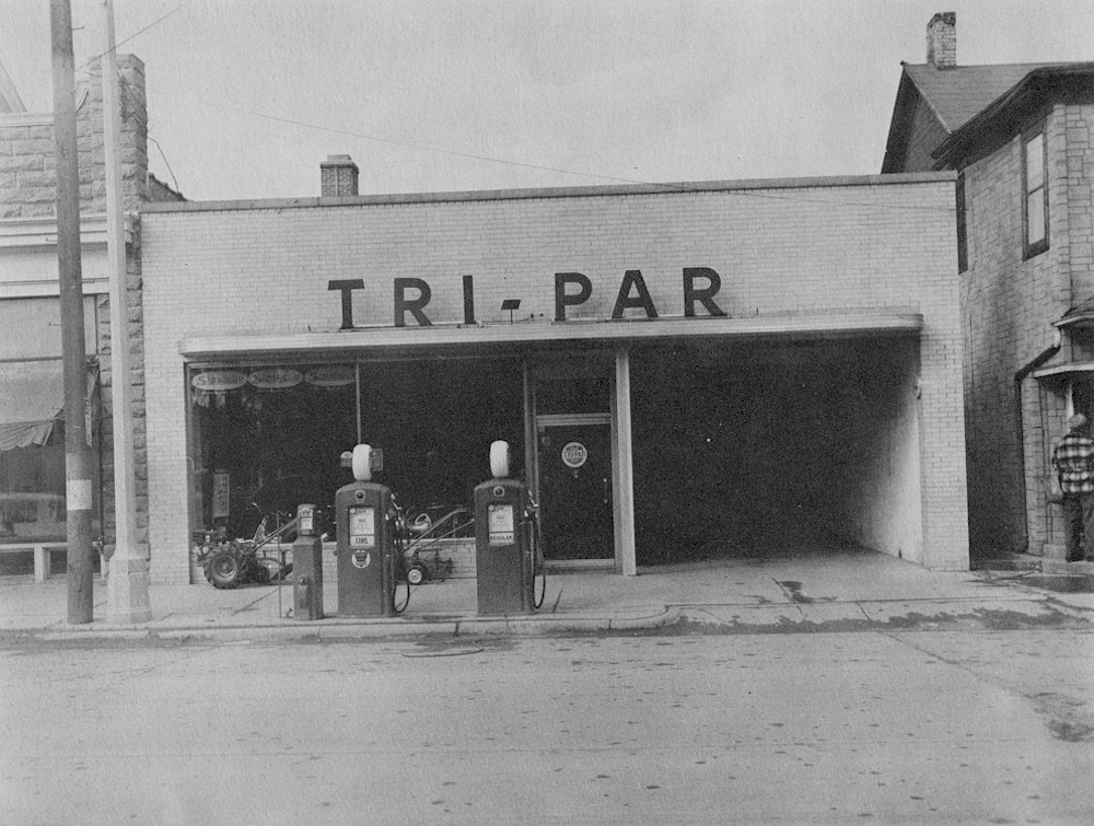 Tri-Par store front with gas pumps and garage door open.